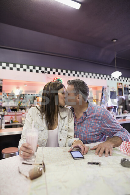 Affectionate mature couple kissing and drinking milkshake at map in soda fountain shop - HEROF03608