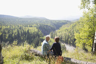 Affectionate mature couple hiking resting on log at sunny remote rural hilltop - HEROF03617