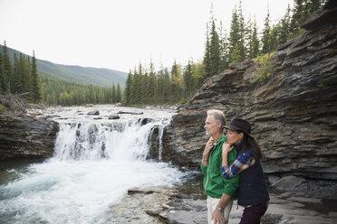 Affectionate couple hugging at waterfall - HEROF03620