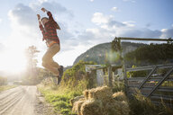 Boy jumping from hay bale on sunny rural farm - HEROF03749