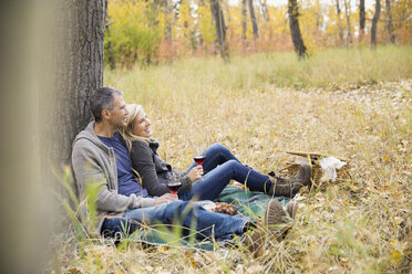 Affectionate couple relaxing enjoying red wine picnic in autumn woods - HEROF03764