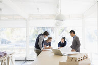 Architects meeting reviewing blueprints at table in office - HEROF03827