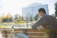 Businessman texting with cell phone on sunny urban park bench - HEROF03839