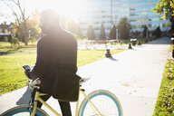 Businessman commuting with bicycle texting with cell phone in sunny urban park - HEROF03842