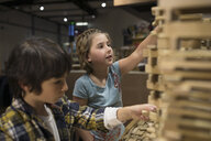 Boy and girl stacking wood pieces in science center - HEROF03851