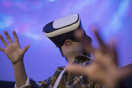 Boy using virtual reality simulator in science center theater - HEROF03857