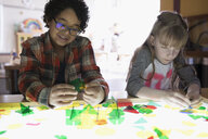 Boy and girl assembling multicolor shapes on lighted display in science center - HEROF03860