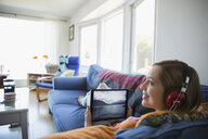 Young woman with headphones on sofa looking at lake photograph on digital tablet - HEROF03869