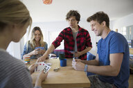 Young couples playing cards at dining table - HEROF03893