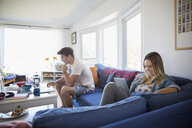 Young couple relaxing using digital tablet and laptop in living room - HEROF03896