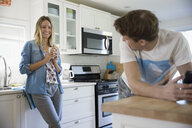 Young couple drinking coffee in kitchen - HEROF03899