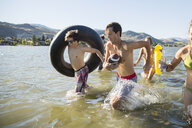 Young friends running with inner tube and football in sunny summer lake - HEROF03911
