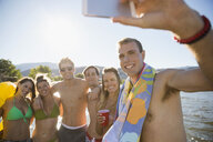 Young friends taking selfie with camera phone at sunny summer lake - HEROF03920