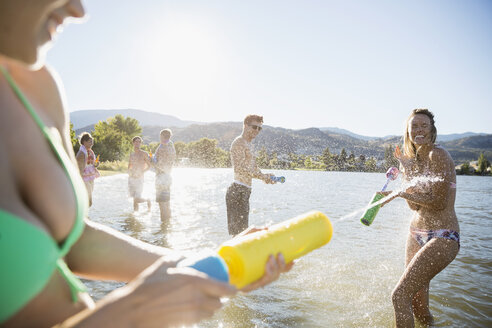 Young friends playing with squirt guns in sunny summer lake - HEROF03926