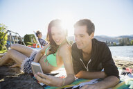 Young couple texting with cell phone on sunny summer beach - HEROF03932