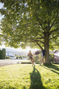 Young couple talking at tree swing in sunny summer yard - HEROF03941