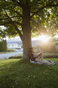 Young woman reading book against tree in summer sunny yard - HEROF03947