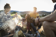 Young friends drinking beer hanging out at campfire on summer beach - HEROF03953