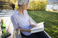 Woman reading book drinking white wine on summer patio - HEROF03965