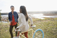 Women with bicycle and insulated drink container talking on autumn hilltop overlooking lake - HEROF04079