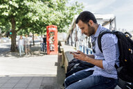 UK, London, man using his smartphone on the street - MGOF03902