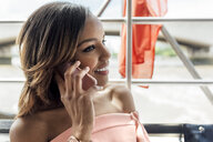 UK, London, portrait of beautiful smiling woman on cell phone while traveling by boat on the River Thames - MGOF03908