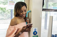 UK, London, smiling beautiful woman using cell phone on the train - MGOF03914
