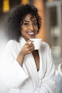 Portrait of smiling young woman drinking coffee in spa - ZEF16100