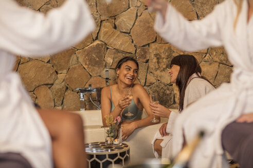 Two happy women having a glass of champagne in a spa - ZEF16103