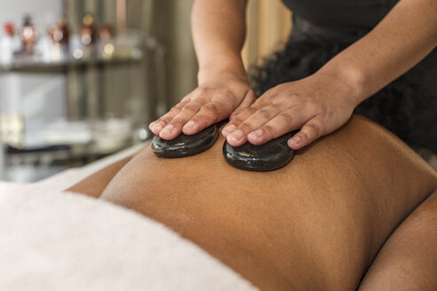 Woman receiving a hot stone massage in a spa - ZEF16109