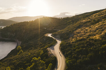 Italy, Elba Island, biker on coastal road against the sun, aerial view with drone - FBAF00216