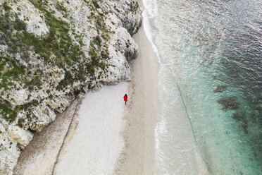 Italy, Elba, woman with red coat walking at beach, aerial view with drone - FBAF00219
