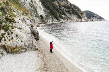 Italy, Elba, woman with red coat taking a photo at beach, aerial view with drone - FBAF00222