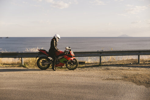 Italy, Elba Island, female motorcyclist at viewpoint - FBAF00231