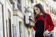 Fashionable young woman looking at cell phone in the city - JSMF00715