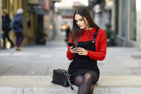 Portrait of fashionable young woman sitting on bench at pedestrian area looking at cell phone - JSMF00721