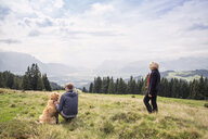 Austria, Tyrol, Kaiser mountains, mother and adult son with dog on a hiking trip in the mountains - MAMF00279