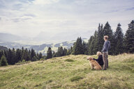 Austria, Tyrol, Kaiser mountains, mother and adult son with dog on a hiking trip in the mountains - MAMF00282