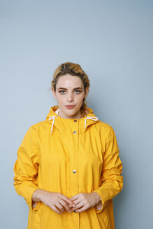 Portrait of young woman wearing yellow rain coat in front of blue background - GRSF00051