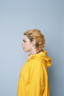 Profile of young woman wearing yellow rain coat in front of blue background - GRSF00054