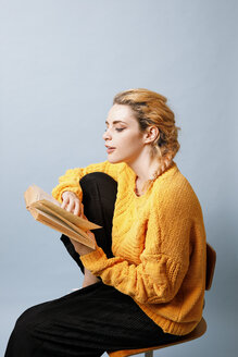 Young woman wearing yellow knit pullover in front of blue background reading a book - GRSF00057