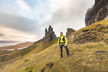 UK, Scotland, Isle of Skye, portrait of smiling man at the The Old Man of Storr on a cloudy day - WPEF01231