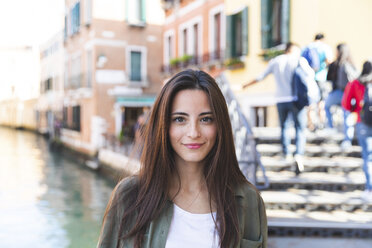 Italy, Venice, portrait of smiling young woman in the city with canal in background - WPEF01237