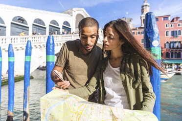 Italy, Venice, couple looking at map with Rialto bridge in background - WPEF01243