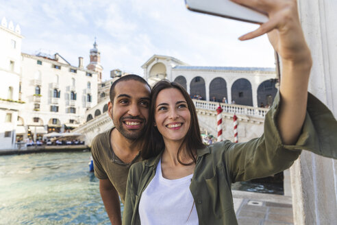 Italy, Venice, couple enjoying the city and taking a selfie with Rialto bridge in background - WPEF01246