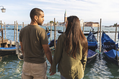 Italy, Venice, affectionate young couple with gondola boats in background - WPEF01249