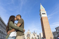 Italy, Venice, tourist couple kissing on St Mark's Square - WPEF01255
