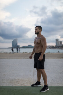 Barechested muscular man standing outdoors at dusk - MAUF02218