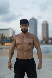 Portrait of barechested muscular man outdoors at dusk - MAUF02233
