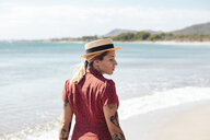 Spain, Mallorca, pensive young woman with tattoos on the beach - LOTF00015
